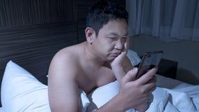 Le téléphone s'est adonné, homme utilisant le téléphone intelligent sur le lit à minuit photo libre de droits