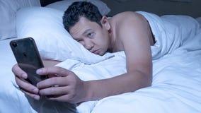 Le téléphone s'est adonné, homme utilisant le téléphone intelligent sur le lit à minuit photo stock