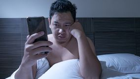 Le téléphone s'est adonné, homme utilisant le téléphone intelligent sur le lit à minuit photos libres de droits