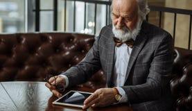 Le ` t de doesn de vieil homme savent utiliser le comprimé Photographie stock libre de droits