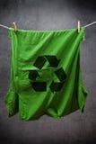 Le T-shirt vert avec réutilisent le symbole accrochant sur la corde pour sécher Photos stock
