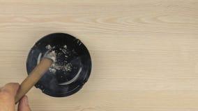 Le tabagisme d'un cigare, pour secouer les cendres, a mis un cigare dans un cendrier banque de vidéos