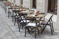 Le Tabelle e le sedie in una fila lungo la parete là sono caffè in immagini stock libere da diritti