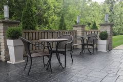 Le Tabelle e le sedie sul patio nella mattina si accendono immagine stock