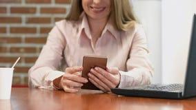 Le tabellen för goda nyheter för läsning för kvinnainnehavsmartphone den sittande, hållande ögonen på video arkivfoto