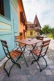 Le Tableau avec des chaises sur la pierre a pavé la vieille rue et a coloré les maisons f Images stock