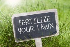 Le tableau dans l'herbe avec fertilisent votre pelouse images stock