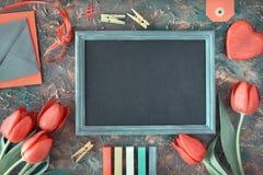 Le tableau noir encadré avec les tulipes rouges, coeur en bois, couleur marque à la craie Photographie stock