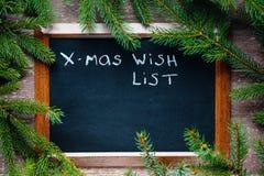 Le tableau noir entouré par le sapin s'embranche avec le list d'envie de Noël des textes Photos stock