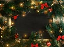 Le tableau noir vide de l'espace entouré par la lumière de Noël, ornementent a images libres de droits