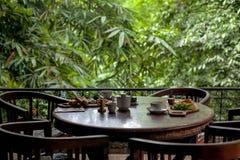 Le Tableau a placé pour le petit déjeuner au restaurant confortable sur la terrasse de verdure dans le style de Bali photographie stock libre de droits
