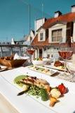Le Tableau pour deux avec la nourriture au restaurant de dessus de toit, les poissons grillés garnissent Photos stock