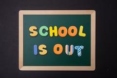 Le tableau vert avec le cadre en bois, école des textes est dans les lettres colorées, fond noir de mur images libres de droits