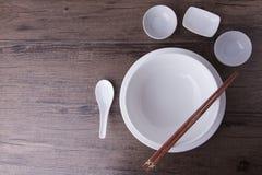 Le tablewear blanc a placé avec des baguettes sur la table en bois Image stock