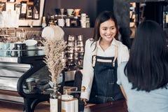 Le tablier asiatique de treillis d'usage de barman de femme tenant la tasse de café a servi au client au compteur de barre avec é photo stock