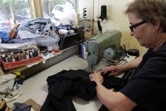 Le tailleur coud des vêtements dans l'atelier de vintage à Sofia, Bulgarie - 9 septembre 2015 Les gens cousent des vêtements Répa Image libre de droits