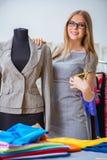 Le tailleur de jeune femme travaillant dans l'atelier sur la nouvelle robe Image stock