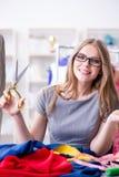 Le tailleur de jeune femme travaillant dans l'atelier sur la nouvelle robe Photo libre de droits