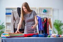 Le tailleur de jeune femme travaillant dans l'atelier sur la nouvelle robe Images libres de droits