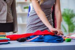 Le tailleur de jeune femme travaillant dans l'atelier sur la nouvelle robe Photos stock