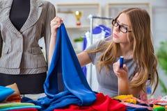 Le tailleur de jeune femme travaillant dans l'atelier sur la nouvelle robe Images stock