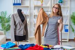 Le tailleur de jeune femme travaillant dans l'atelier sur la nouvelle robe Image libre de droits