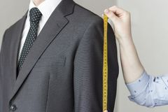 Le tailleur prend des mesures de costume, fond blanc, d'isolement photographie stock