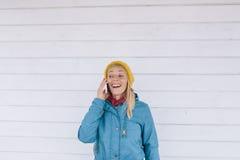 le talande kvinnabarn för telefon kvinnan i guling stack hatten och ett blått omslag genom att använda mobiltelefonen Royaltyfri Bild