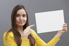 Le 20-talflickan som fokuserar på en annonsering på ett tomt mellanlägg Arkivbilder