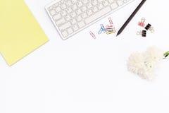 Le tampon jaune, les trombones de clavier et, un crayon et un chrysanthème fleurissent sur un fond blanc Concept plat de configur Photographie stock