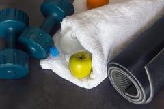 Le tapis noir de yoga, deux haltères et une pomme verte se trouvent sur un St foncé Image stock