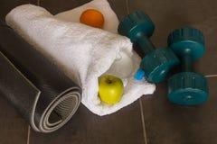 Le tapis noir de yoga, deux haltères et une pomme verte se trouvent sur un St foncé Photos libres de droits