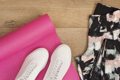 Le tapis rose de yoga, espadrilles femelles, les chaussures de sport, guêtres dans l'appartement étendent le style, vue supérieur Photo stock