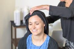 Le tapotement de coiffeur sèchent les cheveux d'une jeune femme image stock