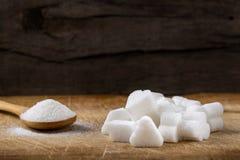 Le tas de différentes formes de cubes en sucre et la cuillère en bois ont rempli esprit Photographie stock libre de droits