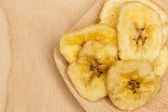 Le tas de la banane sèche ébrèche sur la cuillère en bois Photographie stock libre de droits