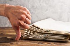 Le tas de vieux journaux empilés et les expositions humaines de main détestent sur la vieille table en bois brune photos stock