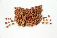 Le tas des aliments pour chats a placé à la forme de visage de chat sur le plancher blanc Les aliments pour chats sont nourriture photographie stock