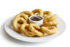 Le tas des anneaux cuits à la friteuse d'oignon ou de calamari avec le barbecue plongent dessus Image libre de droits