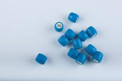 Le tas des barillets en plastique bleus pour le jeu de bingo-test avec des nombres s'étendent sur le fond blanc Photo libre de droits