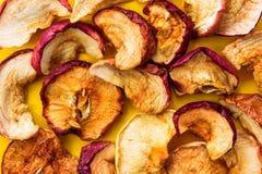 Le tas des fruits séchés au soleil organiques a déshydraté des pommes dispersées sur le fond jaune lumineux Aliments complets d'a image stock