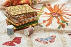 Le tas des morceaux piquant des tissus s'étendent sur le tissu avec des fleurs et des images de papillon photographie stock libre de droits