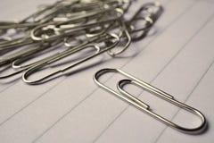 Le tas des trombones en métal sur le blanc a rayé le bloc-notes de papier comme symbole d'environnement typique de bureau Image libre de droits