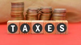 Le tasse esprimono sui blocchi di legno con valuta nel fondo Fotografia Stock
