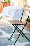 Le tavole bianche con la sedia all'estate svuotano il caffè dell'aria aperta in Grecia Fotografia Stock