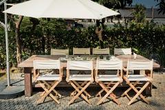 Le tavole, le sedie e gli ombrelli vuoti nel giardino per il BBQ fanno festa Fotografia Stock