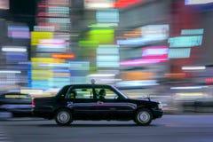 Le taxi avec la lumière traîne le fond de tache floue de mouvement Images stock