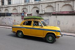 Le taxi jaune iconique Kolkata d'ambassadeur avec un toit d'herbe Photographie stock