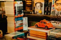 Le taxi orange de Volkswagen Coccinelle de vintage de couleur modèle sur la pile de b Photo libre de droits
