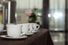 le tazze bianche di tè sono in una fila sulla tavola con una tovaglia marrone fotografia stock libera da diritti